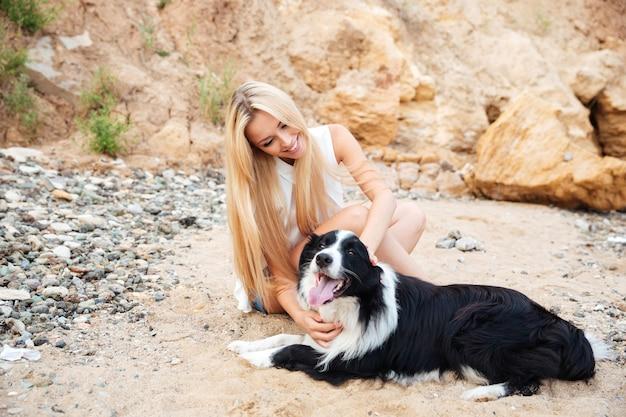 Wesoła śliczna młoda kobieta siedzi z psem na plaży