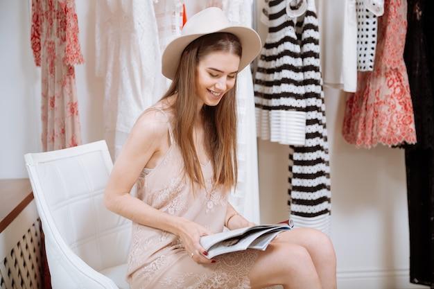 Wesoła śliczna młoda kobieta w kapeluszu czytania magazynu w sklepie z ubraniami
