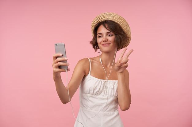Wesoła śliczna młoda kobieta z krótkimi brązowymi włosami w letnich ubraniach i słuchawkach, trzymając smartfon i podnosząc rękę gestem zwycięstwa podczas robienia selfie, na białym tle