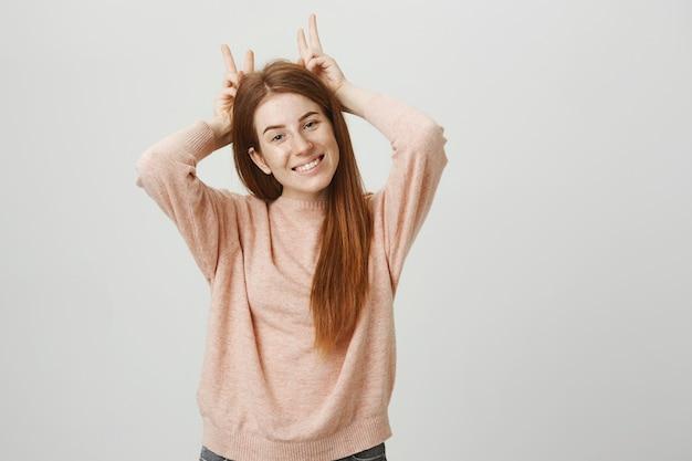 Wesoła śliczna ruda dziewczyna pokazuje rogi nad głową i uśmiecha się