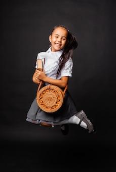 Wesoła śliczna uczennica trzyma książkę i okrągłą torbę i skacze na ciemnym tle.