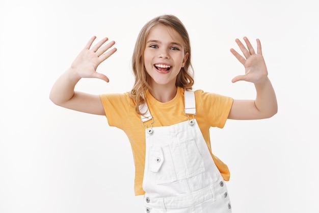 Wesoła śliczna zabawna blond dziewczynka bawi się, bawi się podnosząc dłonie, pokazuje czyste ręce, uśmiechając się szeroko, wygłupia się, ciesz się wakacjami, wygląda na rozbawioną i podekscytowaną, stoi na białej ścianie