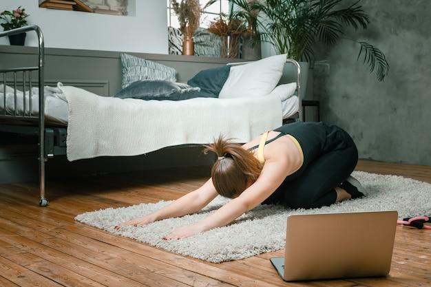 Wesoła sportowa kobieta o czarnych włosach rozciąga się do nogi w sypialni