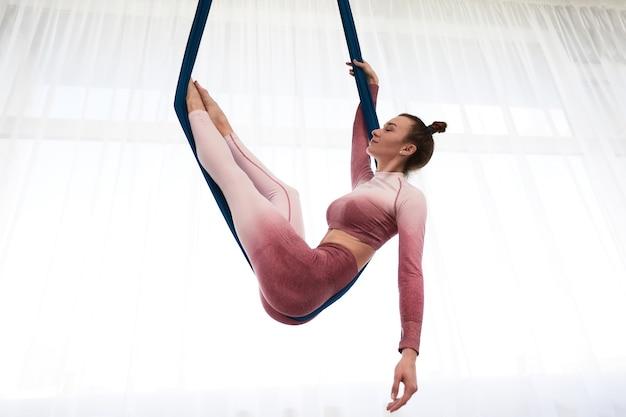 Wesoła, sportowa kobieta ubrana w top i legginsy, wykonująca antygrawitacyjne ćwiczenia jogi w przestronnym klubie fitness z panoramicznymi oknami.