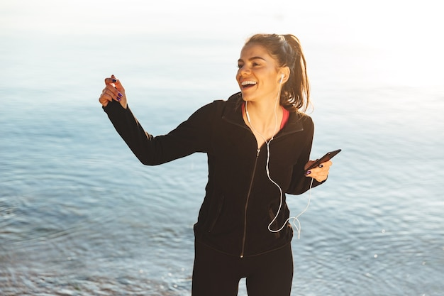 Wesoła sportsmenka, słuchanie muzyki przez słuchawki