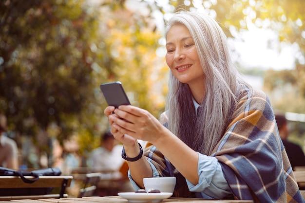 Wesoła starsza azjatycka kobieta pisze sms na smartfonie siedząc przy stole