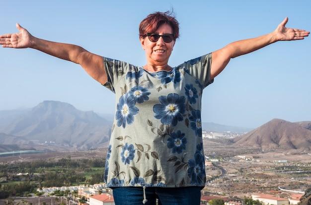 Wesoła starsza kobieta ciesząca się wolnością stojącą na wzgórzu z górą i miastem w tle