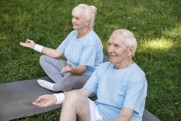 Wesoła starsza kobieta i mężczyzna medytują siedząc w lotosowych pozach na trawniku