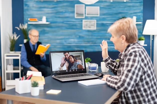 Wesoła starsza kobieta macha przed kamerą internetową podczas rozmowy online z krewnymi