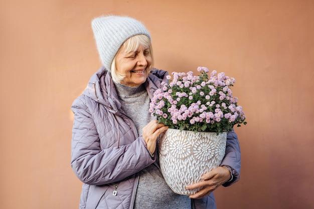 Wesoła starsza kobieta robi hobby i lubi ogrodnictwo. wieku kobieta niosąca kwiaty doniczkoweted