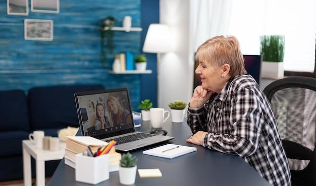 Wesoła starsza kobieta rozmawiająca z wnuczką podczas wideokonferencji