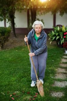Wesoła starsza kobieta trzyma miotłę na podwórku domu.