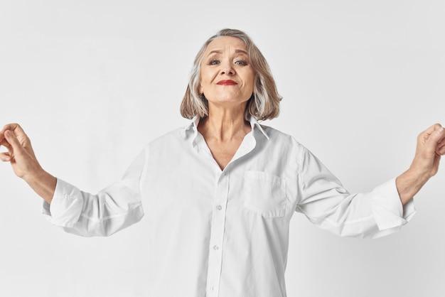 Wesoła starsza kobieta w białej koszuli emocje studio styl życia. zdjęcie wysokiej jakości