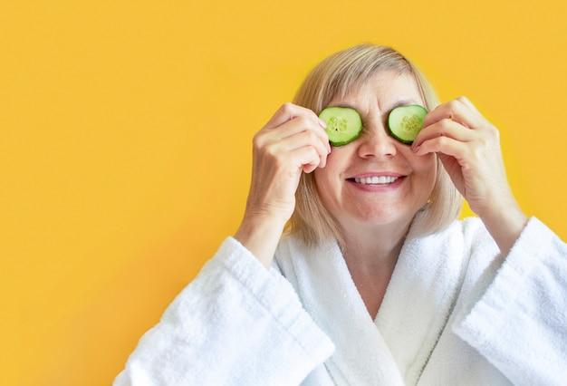 Wesoła starsza kobieta z plasterkami ogórka zasłaniające oczy przed oczami na żółtym tle. zabiegi spa w domu, koncepcja pielęgnacji ciała, kosmetyki organiczne. naturalne leczenie uzdrowiskowe.