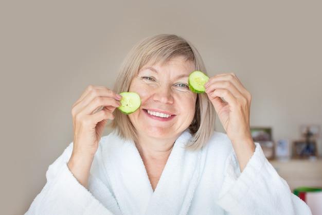 Wesoła starsza kobieta z plasterkami ogórka zasłaniające oczy przed oczami w jej sypialni. zabiegi spa w domu, koncepcja pielęgnacji ciała, kosmetyki organiczne. naturalne leczenie uzdrowiskowe.