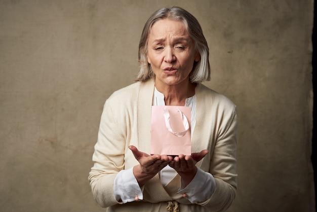 Wesoła starsza kobieta z torbą na prezenty wakacyjne studio
