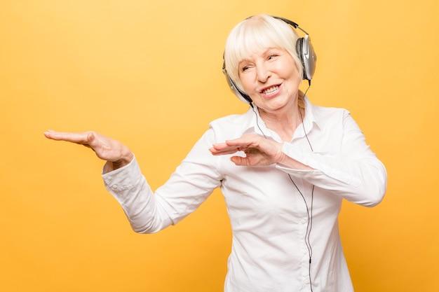 Wesoła starsza kobieta ze słuchawkami, słuchanie muzyki w telefonie i taniec na białym tle na żółtym tle.