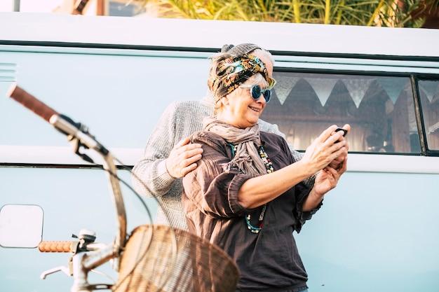 Wesoła starsza piękna kobieta z dojrzałym mężem ciesz się telefonem