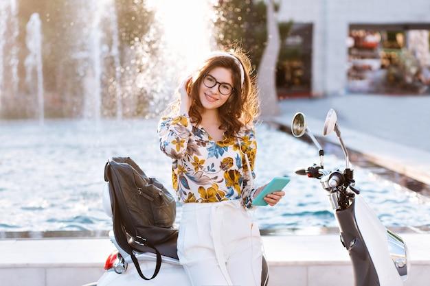 Wesoła studentka w okularach i stylowy wiosenny strój pozuje z uśmiechem przed fontanną