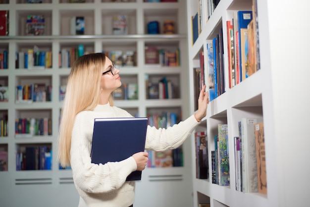 Wesoła studentka w okularach stojących w pobliżu półek z książkami w nowoczesnej bibliotece wnętrza uniwersytetu podczas przerwy między lekcjami