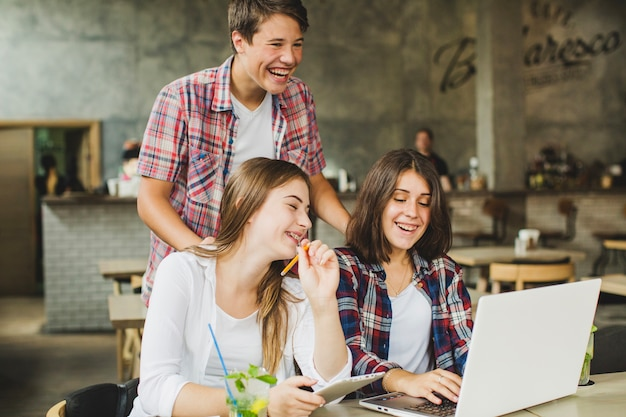 Wesoła studentów stwarzających z komputera przenośnego