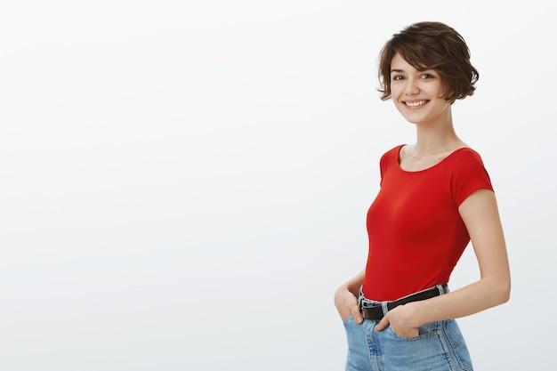 Wesoła stylowa dziewczyna uśmiecha się szczęśliwy w aparacie