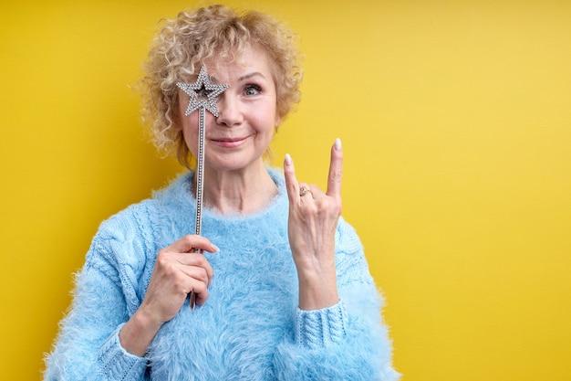 Wesoła, szalona starsza kobieta z magiczną różdżką, pokazująca rockowy gest, uśmiechnięta, pozująca na białym tle
