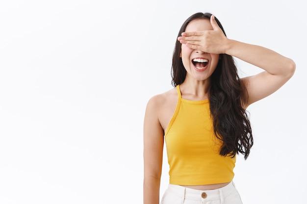 Wesoła, szczęśliwa, beztroska wschodnia azjatka zakrywa oczy dłonią i uśmiecha się rozbawiona, czekając na urodzinową niespodziankę lub biorąc udział w konkursie halloweenowym, nie zerkając na coś ciekawego