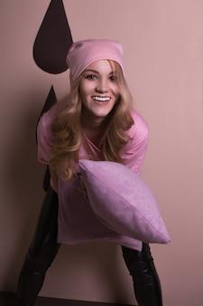 Wesoła szczęśliwa blondynka bawiąca się poduszkami na różowym tle studia