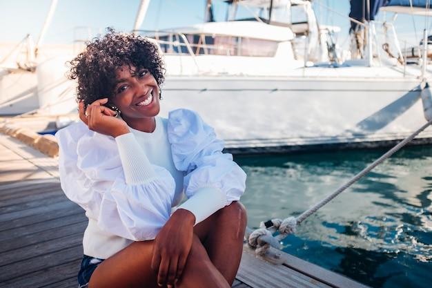 Wesoła, szczęśliwa czarna afrykańska młoda kobieta siada uśmiechnięta na zewnątrz