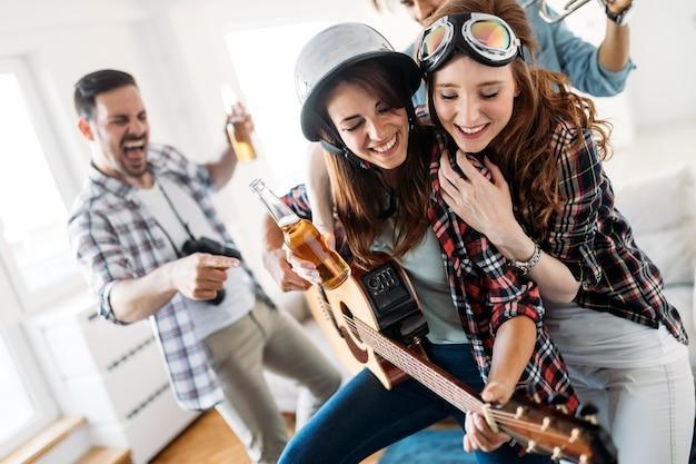 Wesoła szczęśliwa grupa przyjaciół bawiących się podczas gry na instrumentach i picia