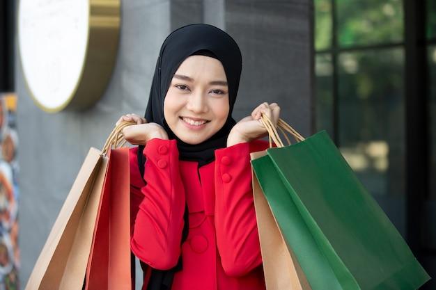 Wesoła szczęśliwa kobieta ciesząca się zakupami niesie torby na zakupy