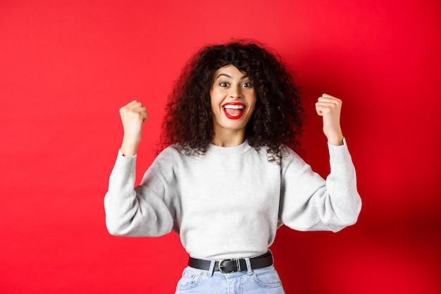 Wesoła szczęśliwa kobieta z kręconymi włosami, wygrywająca nagrodę i krzycząca tak z radości, podnosząca ręce i świętująca, triumfująca i wiwatująca, stojąca na czerwonym tle.