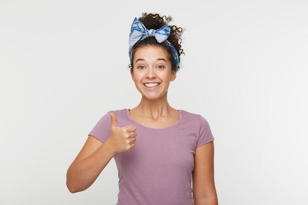 Wesoła szczęśliwa młoda dziewczyna z kręconymi włosami, zębatym uśmiechem, wyraźnie szczęśliwa i optymistyczna