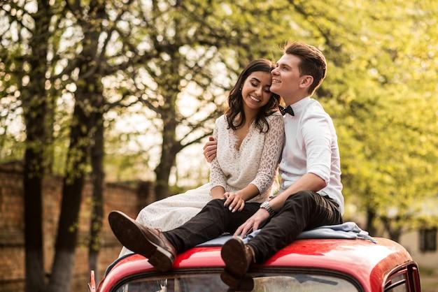 Wesoła szczęśliwa młoda para siedzi na dachu samochodu