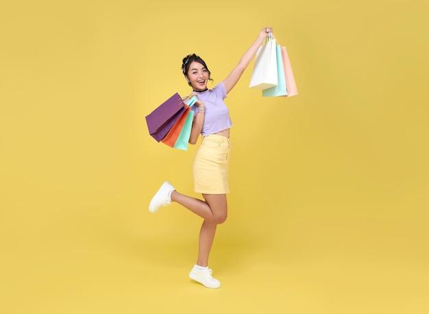 Wesoła, szczęśliwa nastolatka azjatka korzystająca z zakupów, nosi torby na zakupy, aby uzyskać najnowsze oferty w centrum handlowym.