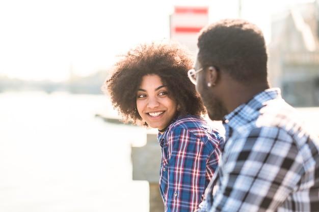 Wesoła szczęśliwa piękna dziewczyna czarna rasa afrykańska z afro włosami uśmiechem i ciesz się z chłopakiem w słonecznej aktywności na świeżym powietrzu