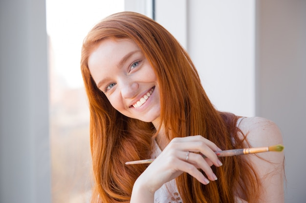 Wesoła szczęśliwa piękna ruda młoda kobieta z długimi włosami stoi schludne okno