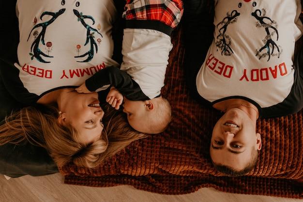 Wesoła szczęśliwa rodzina w piżamie z dzieckiem leży na łóżku w sypialni. noworoczne ubrania rodzinne wyglądają stroje. prezenty na walentynki