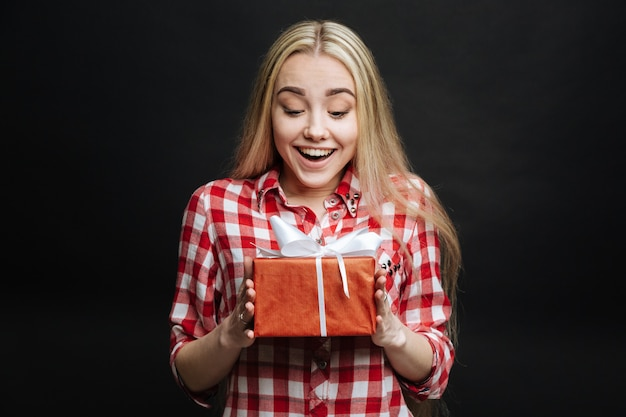 Wesoła, szczęśliwa, szczera dziewczyna wyrażająca zachwyt i odbierająca pudełko, stojąc przed czarną ścianą