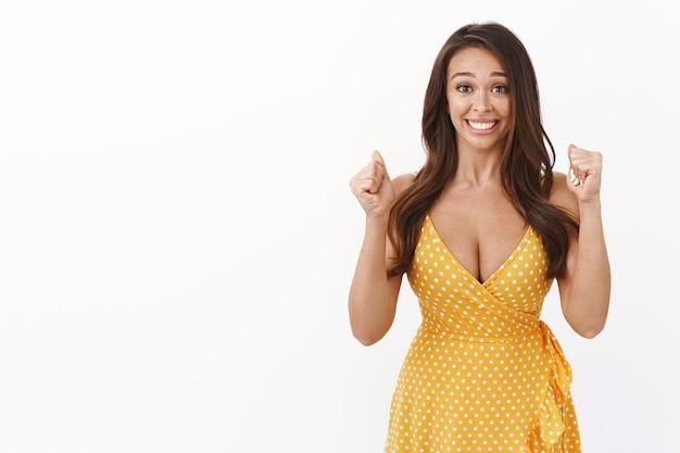 Wesoła, szczęśliwa, urocza kobieca dziewczyna z piegami w żółtej sukience, z radością pompująca pięść, uśmiechnięta z ulgą i satysfakcją, osiągająca cel, wygrywająca nagrodę, świętująca zwycięstwo, triumfująca biała ściana