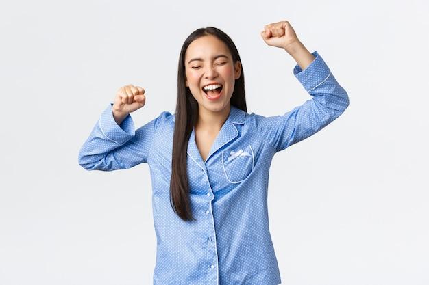 Wesoła triumfująca azjatycka kobieta w niebieskiej piżamie śpiewająca, uśmiechająca się i krzycząca tak zachwycona lub z ulgą, podnosząca ręce w górę w sukcesie i zwycięstwie, świętująca wspaniałe wieści, białe tło