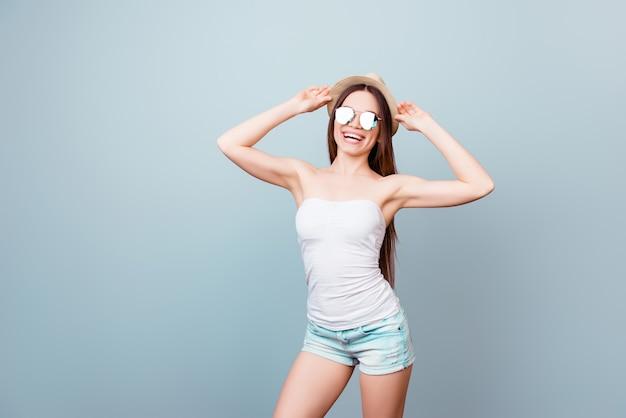 Wesoła turystka brunetka ypung trzyma swoją czapkę, stoi w ładnej seksownej pozie, tak uroczej, z ładną figurą i zębatym uśmiechem, na czystej niebieskiej przestrzeni