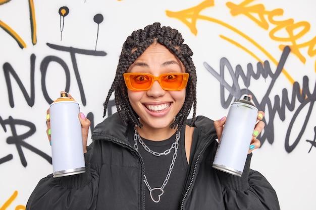 Wesoła tysiącletnia kobieta z warkoczami trzyma dwie butelki z aerozolem będąc kreatywnym artystą ulicznym rysuje graffiti, nosi modne ubrania pomarańczowe okulary przeciwsłoneczne należą do gangu