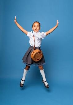 Wesoła uczennica 7 lat z torbą na ramieniu, skacząca na niebieskim tle.