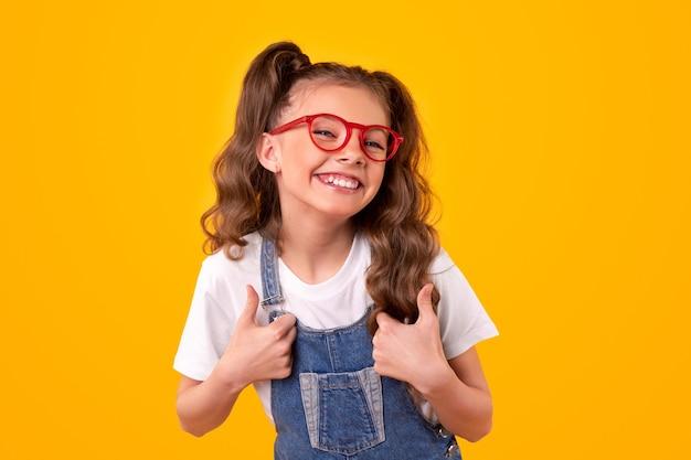 Wesoła uczennica gestykuluje aprobaty w okularach