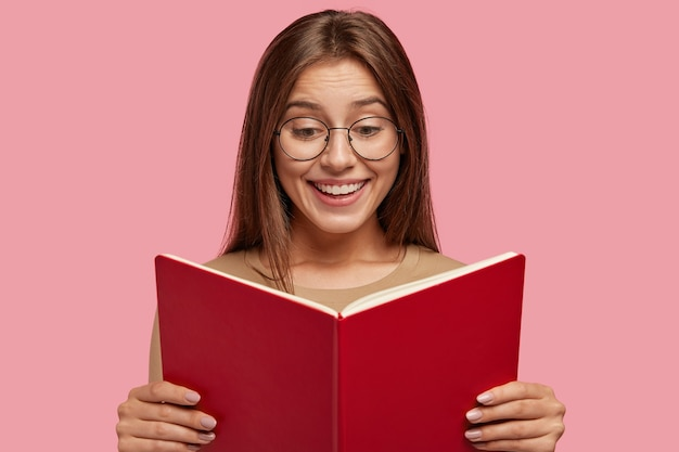 Wesoła uczennica trzyma podręcznik, czyta ciekawą książkę