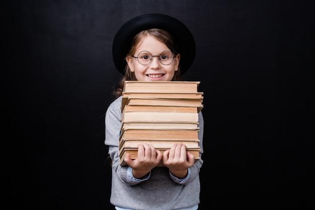 Wesoła uczennica z uśmiechem toothy trzymając stos książek, stojąc w izolacji przed czarną przestrzenią