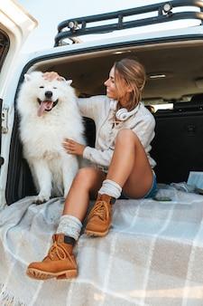 Wesoła urocza dziewczyna bawi się z psem siedząc w samochodzie na plaży