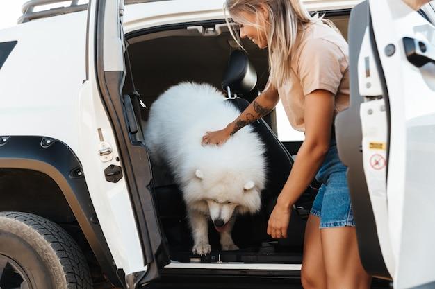 Wesoła urocza dziewczyna bawi się z psem, stojąc przy swoim samochodzie na plaży